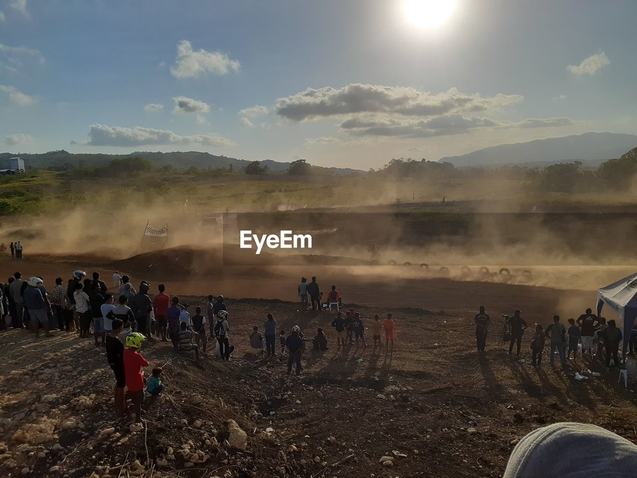 crowd, large group of people, real people, group of people, environment, smoke - physical structure, sky, nature, men, land, day, landscape, environmental issues, heat - temperature, lifestyles, sunlight, outdoors, field, women, pollution, lens flare, hot spring, dust