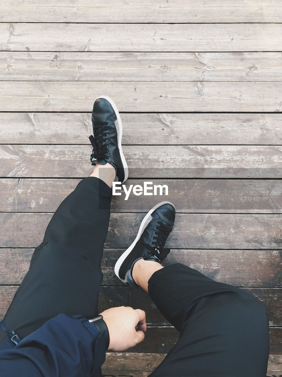 low section, shoe, human leg, real people, human body part, body part, lifestyles, wood - material, people, personal perspective, men, high angle view, footpath, day, leisure activity, two people, sitting, adult, black color, outdoors, human foot, wood, jeans