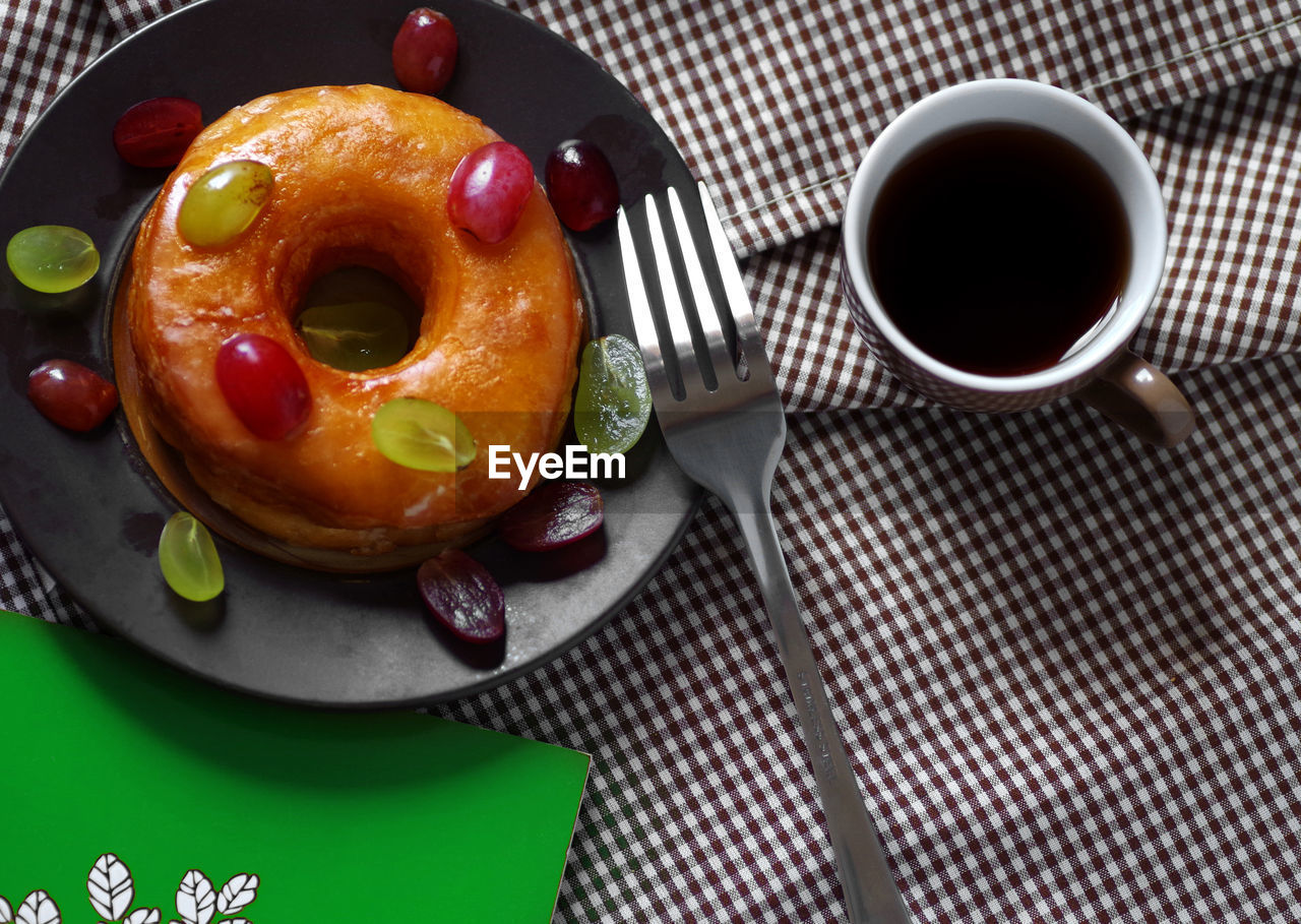 High angle view of black coffee by donut in plate on table