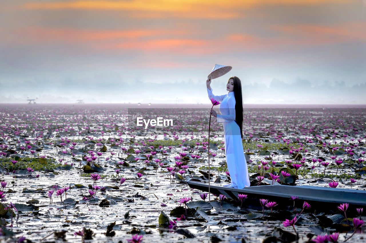 Side view portrait of young woman on boat amidst pink water lilies in lake
