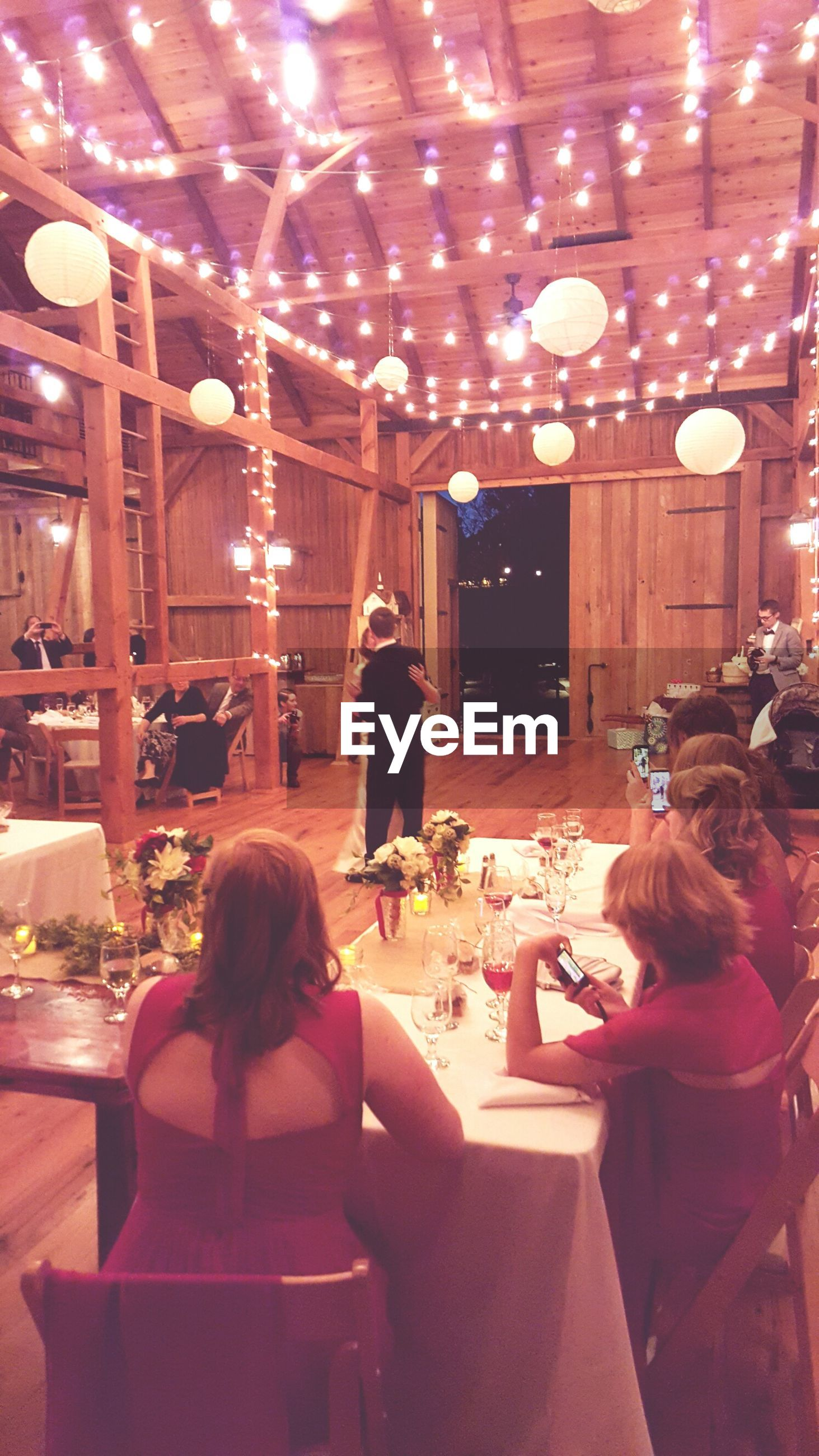 lifestyles, illuminated, indoors, leisure activity, person, men, rear view, night, togetherness, sitting, casual clothing, celebration, lighting equipment, standing, table, restaurant, enjoyment, full length