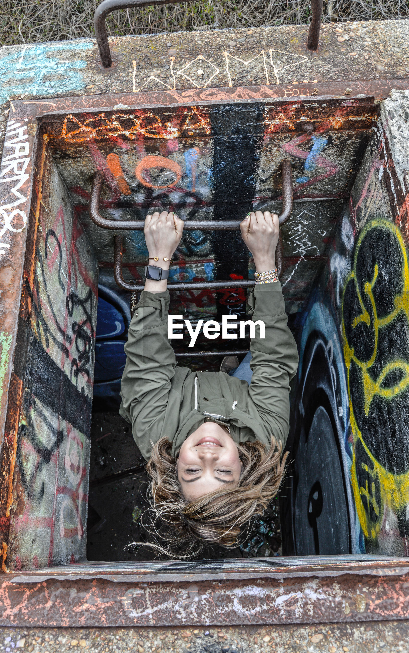 High angle view of woman at sewer with graffiti