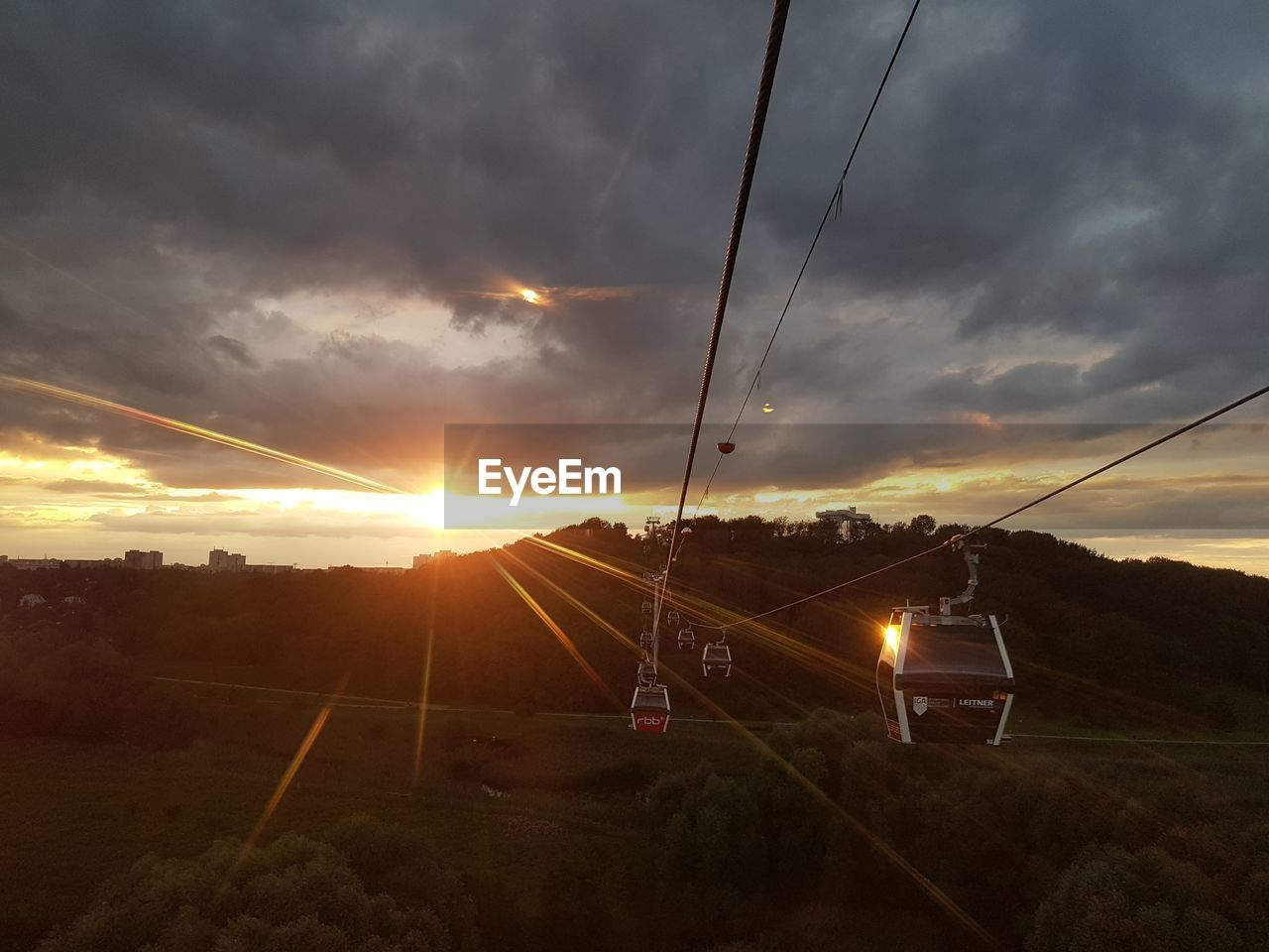sunset, transportation, sky, cable, cloud - sky, sun, nature, scenics, mode of transport, no people, beauty in nature, connection, outdoors, landscape, sunlight, overhead cable car, travel destinations, technology, storm cloud, telephone line, day