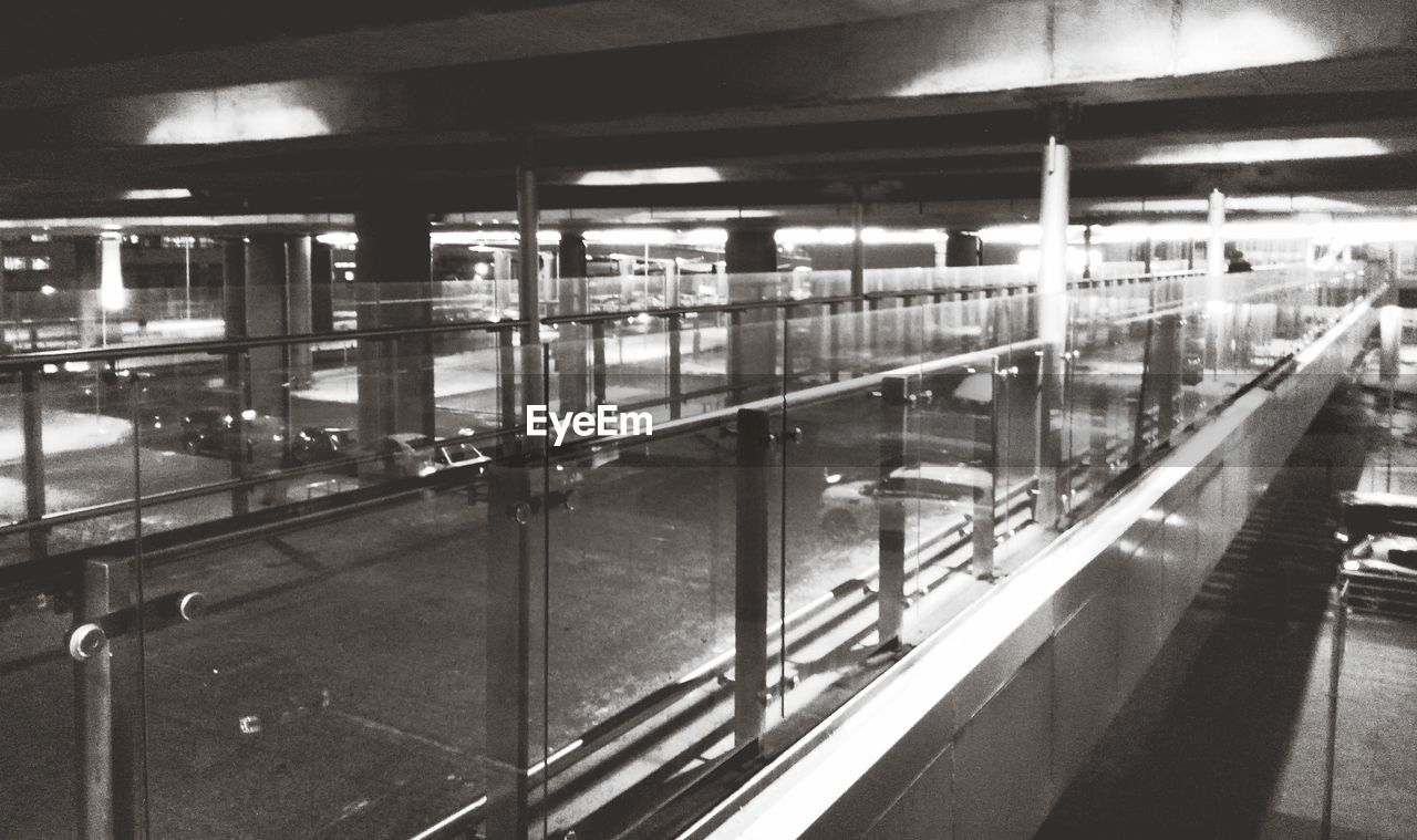 illuminated, indoors, railing, built structure, architecture, night, real people, subway station, parking garage