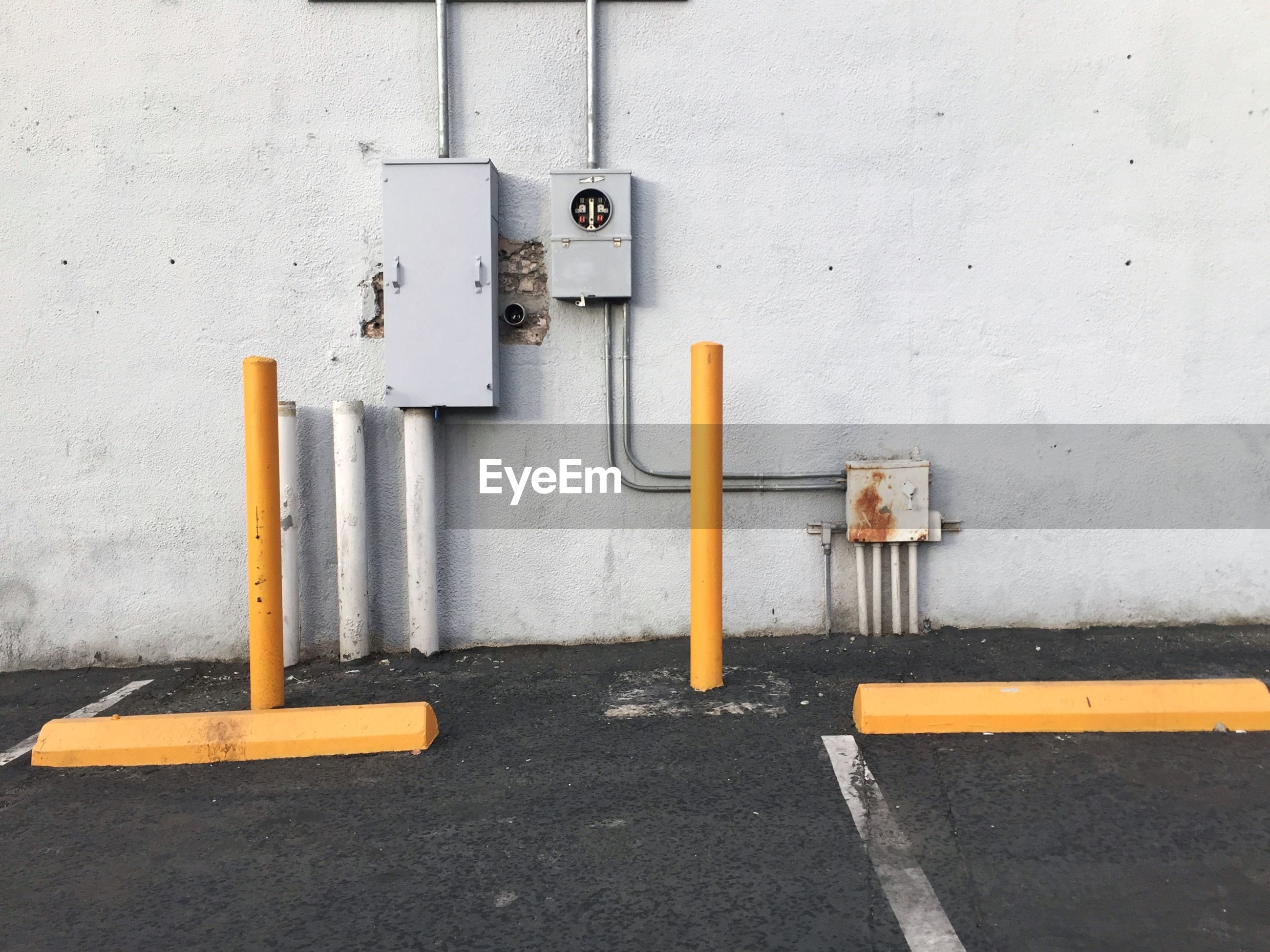 Poles against wall at parking lot