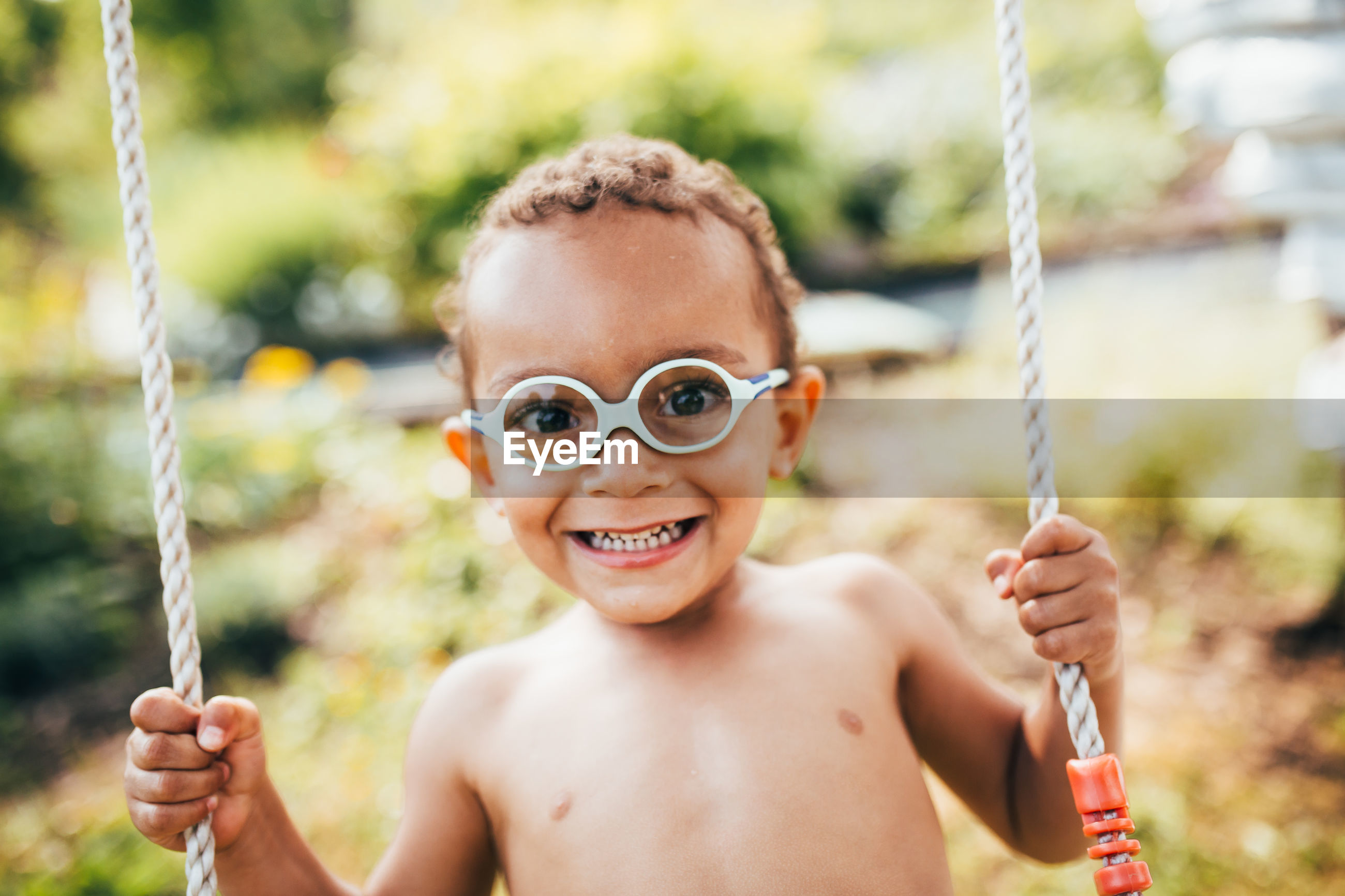 Portrait of shirtless boy sitting on swing against trees