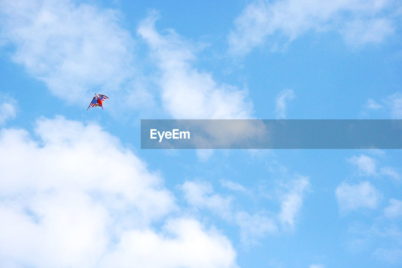 cloud - sky, sky, low angle view, flying, kite, day, mid-air, outdoors, childhood, nature, blue, beauty in nature, no people