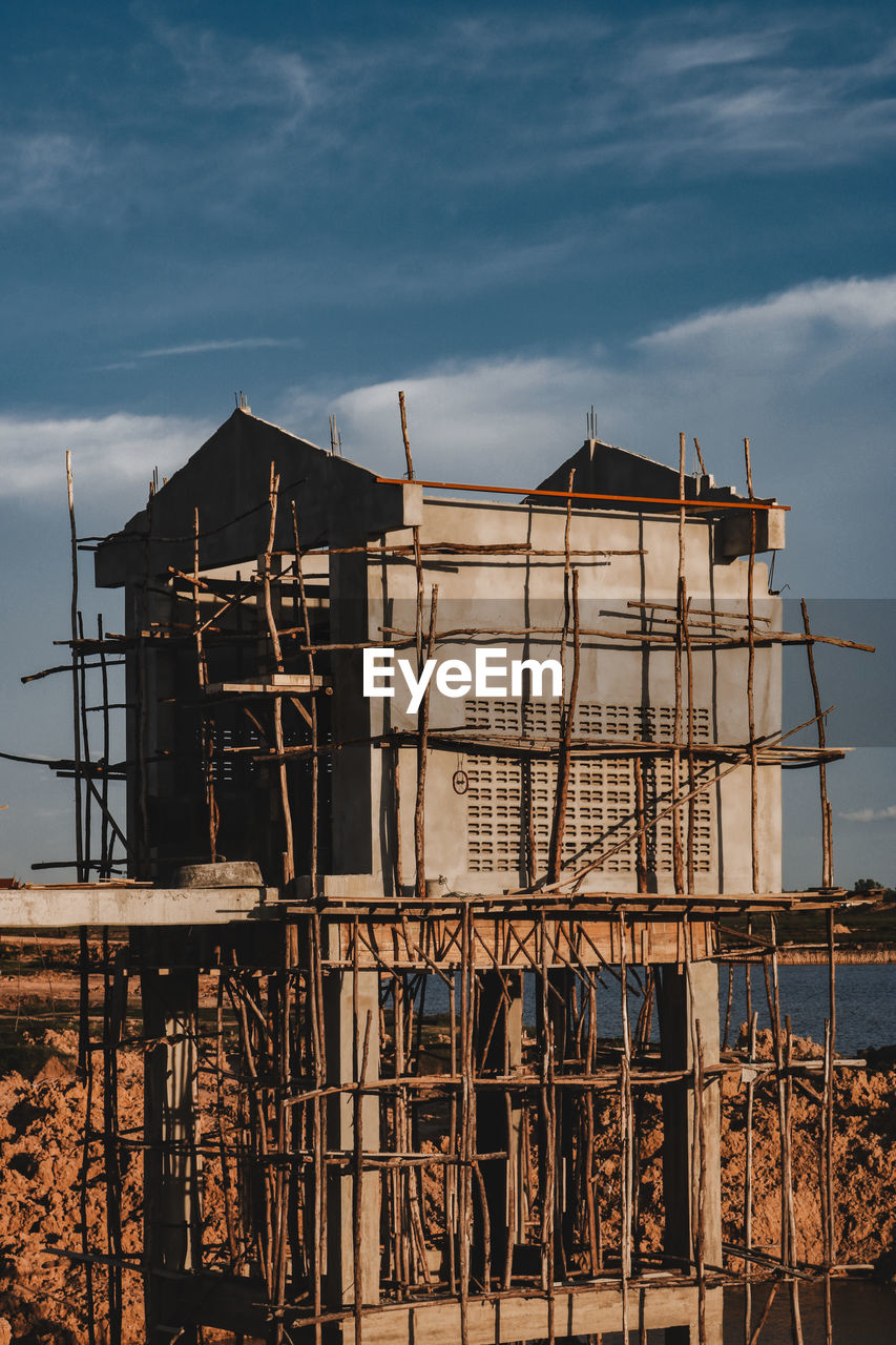 built structure, architecture, sky, building exterior, cloud - sky, building, no people, nature, industry, day, residential district, house, outdoors, wood - material, construction industry, abandoned, construction site, sunlight, stilt house, damaged, ruined, home improvement