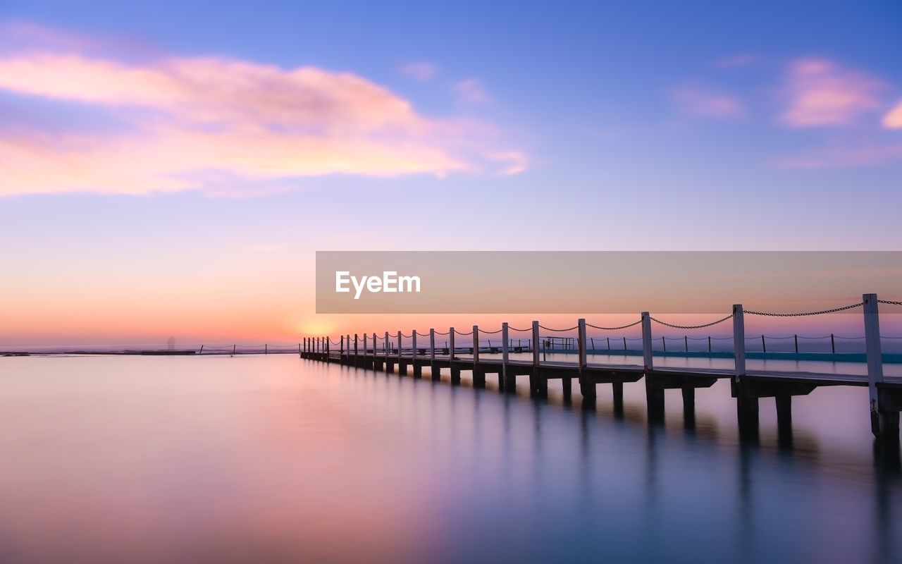sky, water, sunset, scenics - nature, beauty in nature, waterfront, cloud - sky, orange color, sea, architecture, tranquil scene, pier, tranquility, nature, no people, built structure, reflection, idyllic, transportation, outdoors, wooden post