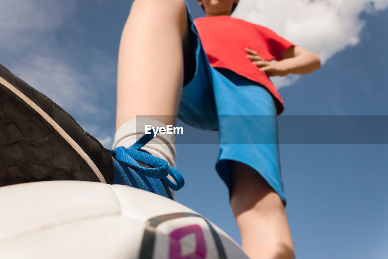 Low section of boy standing on ball against blue sky