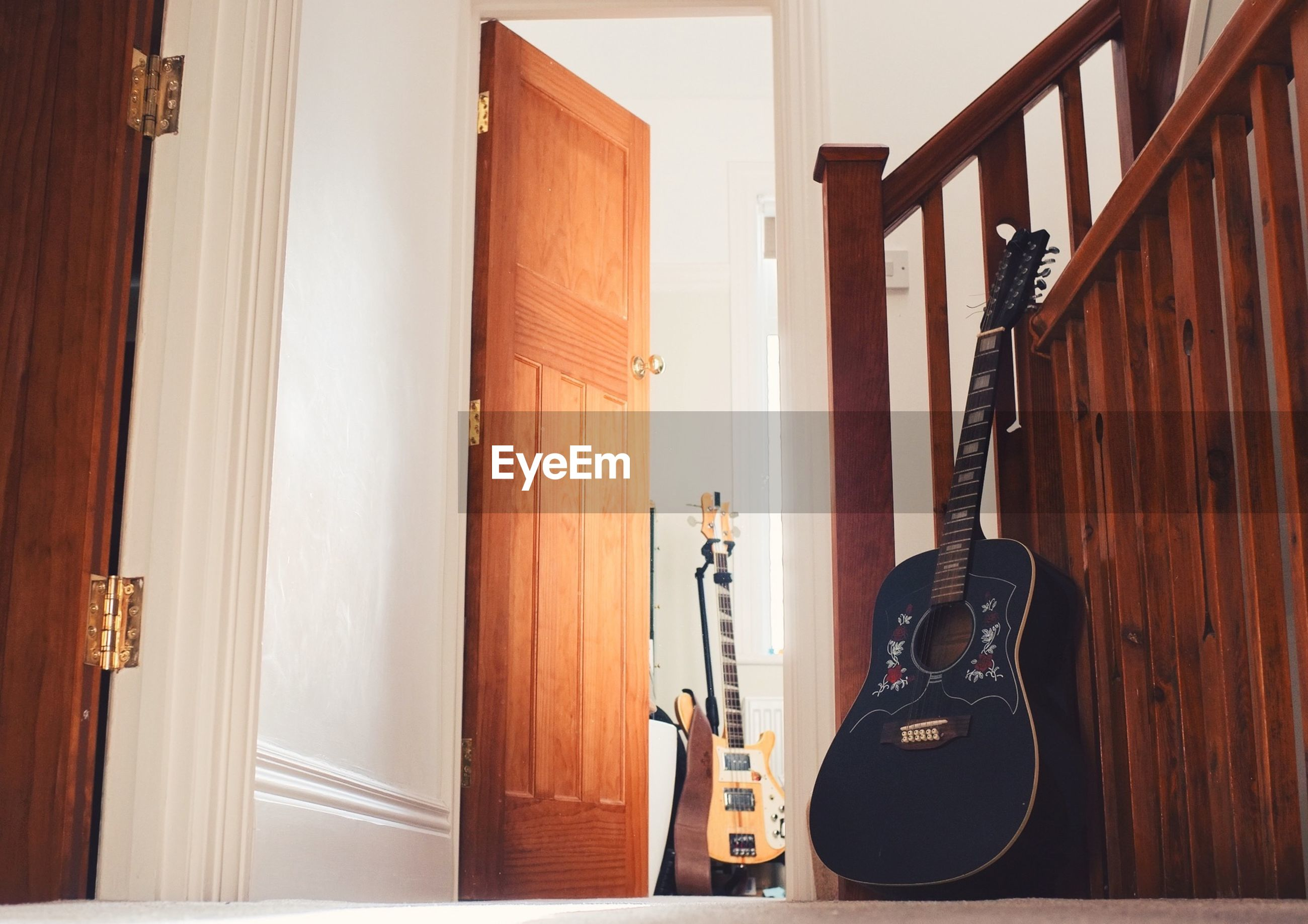 Guitar by wooden railing at home