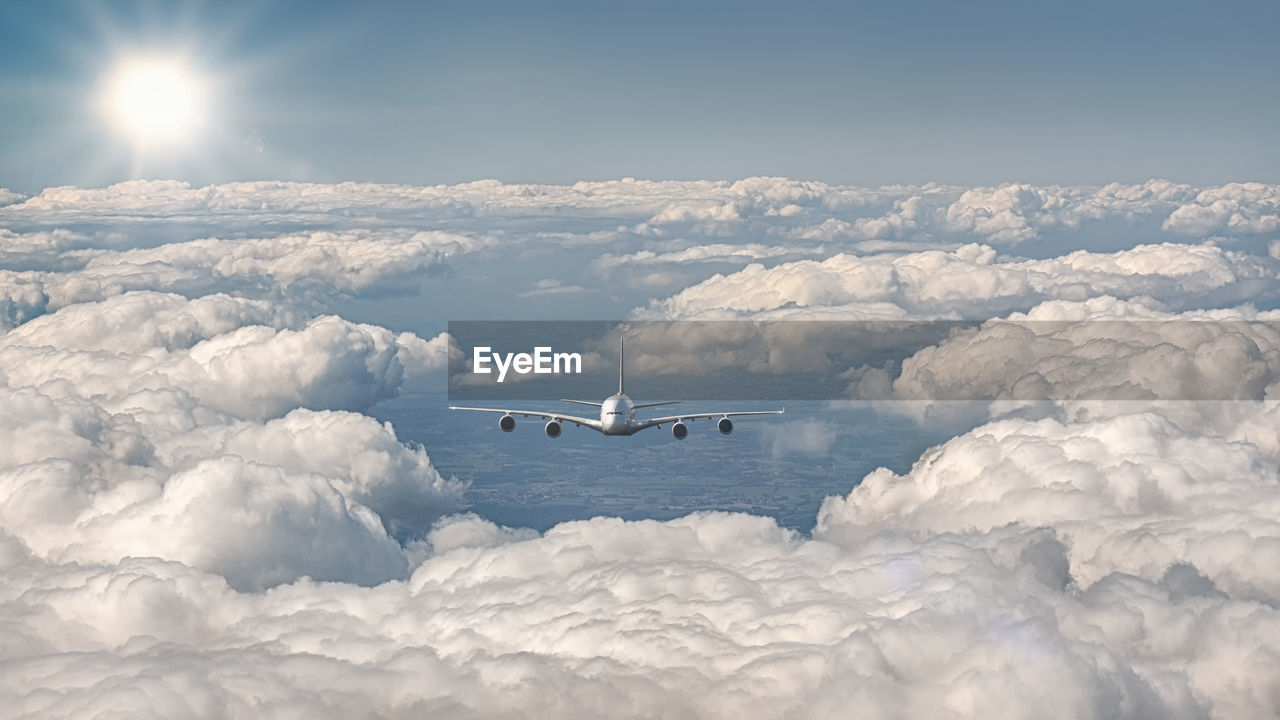 Exterior view of an airplane flying over the clouds