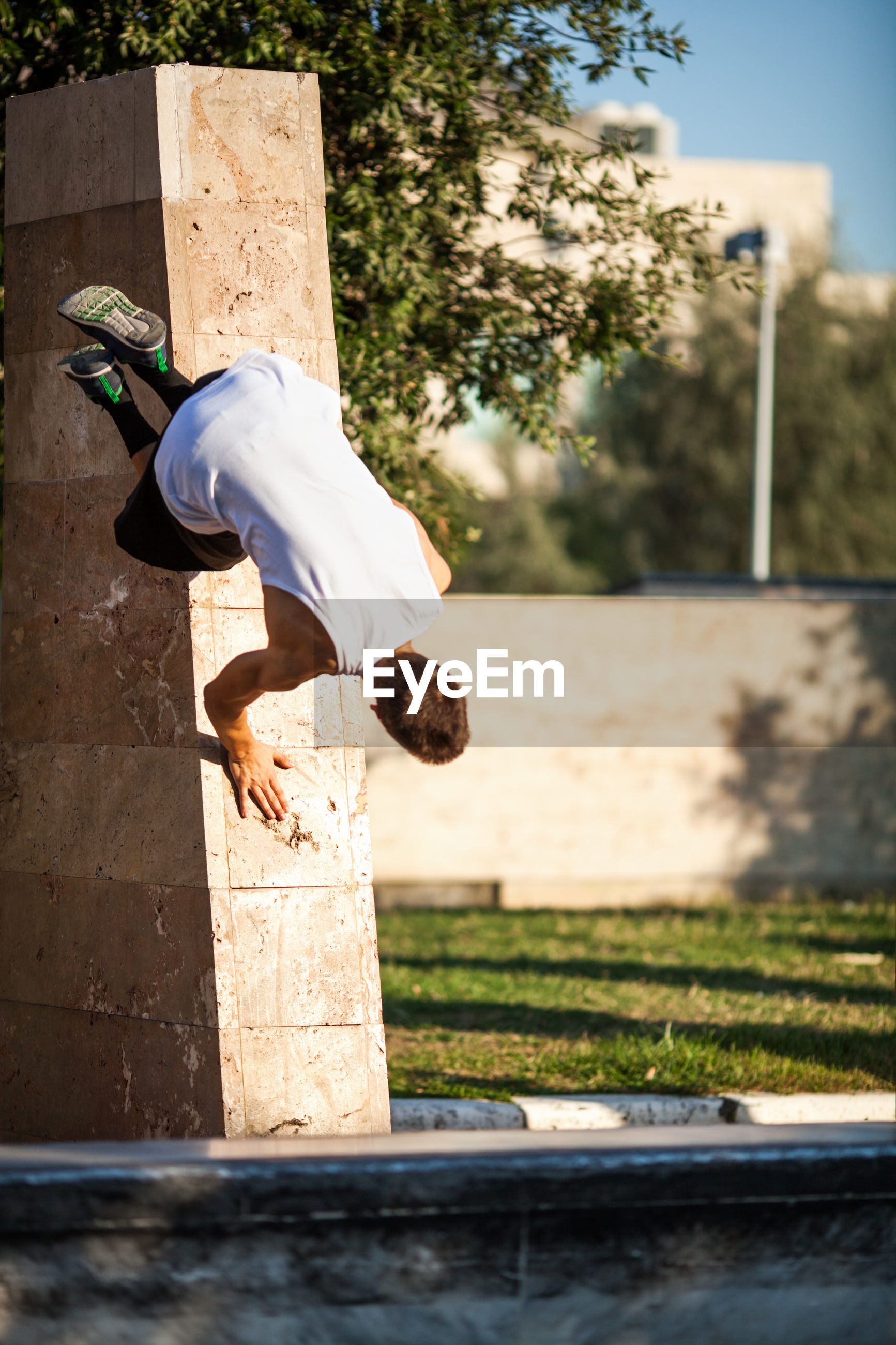 Young man doing stunt on retaining wall in park