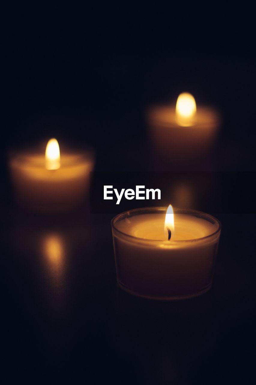 Close-up of tea light candles burning in darkroom