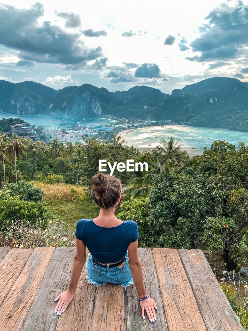 REAR VIEW OF WOMAN SITTING ON WOOD LOOKING AT MOUNTAINS
