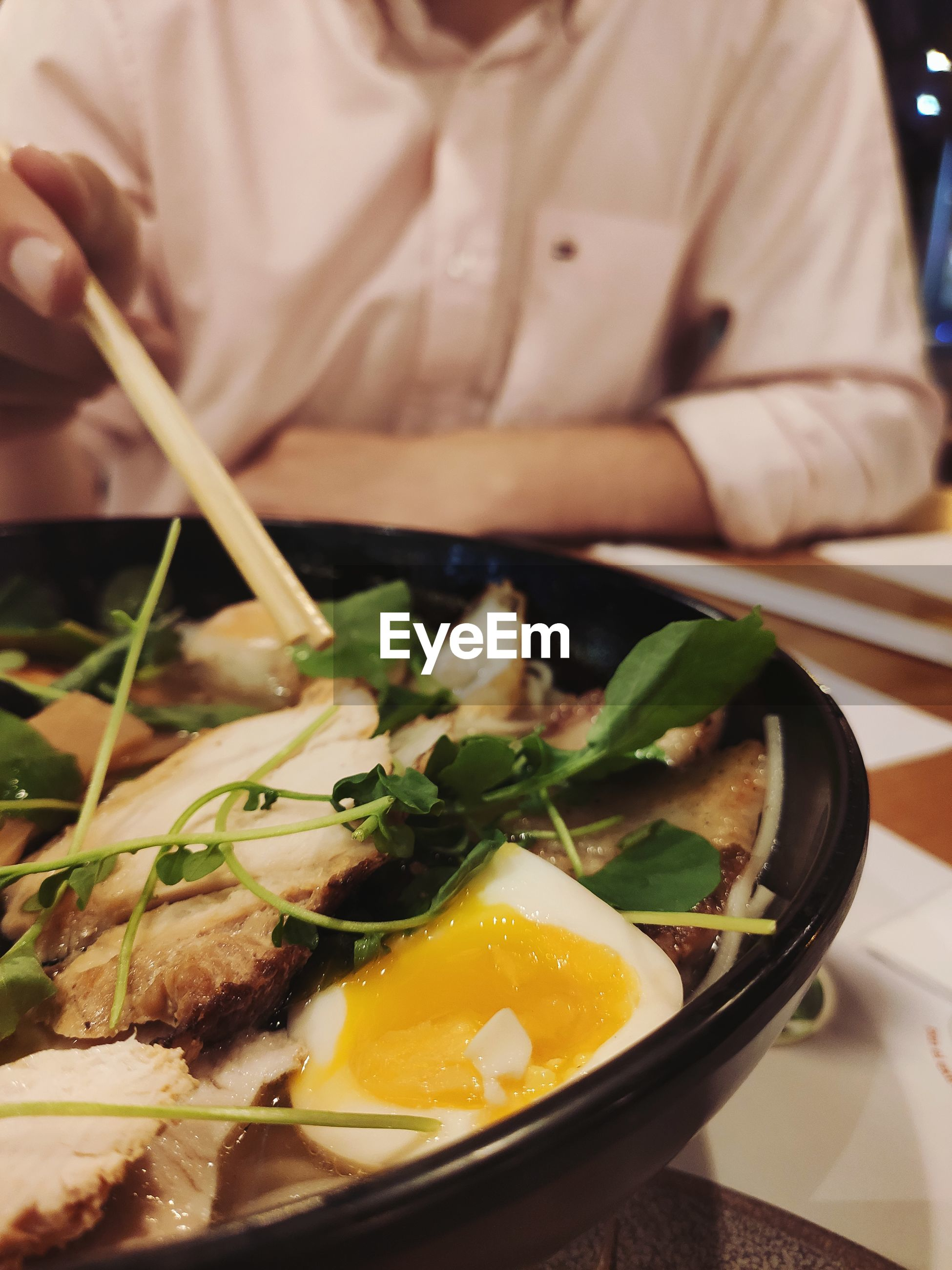 Close-up of ramen served in plate man eating with chopsticks