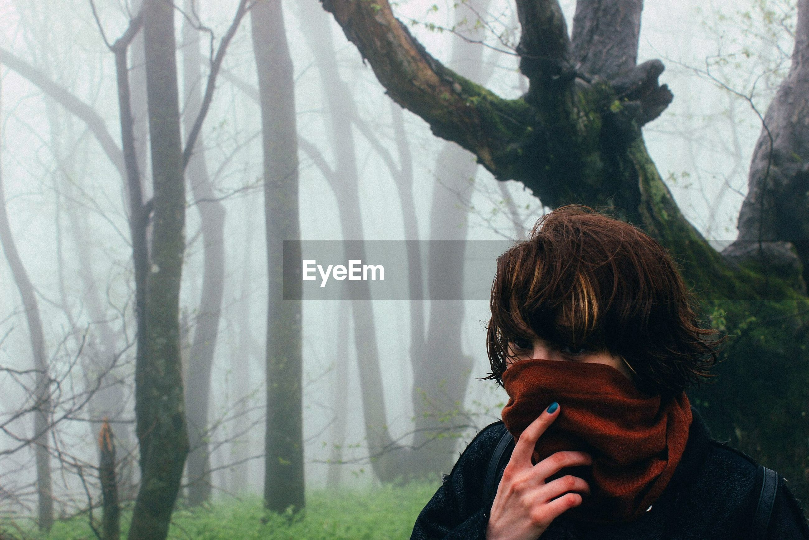 Close-up of woman with covered face against bare trees in foggy weather