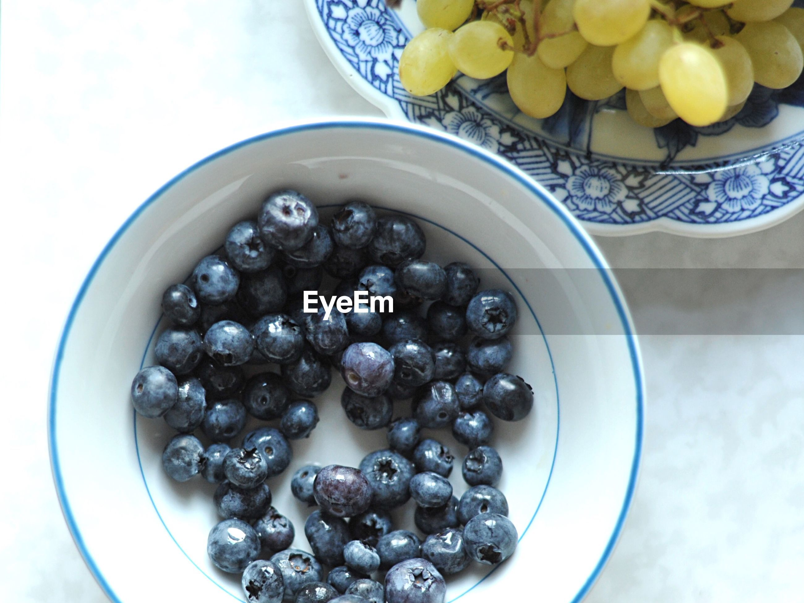 High angle view of blueberries and grapes in bowl