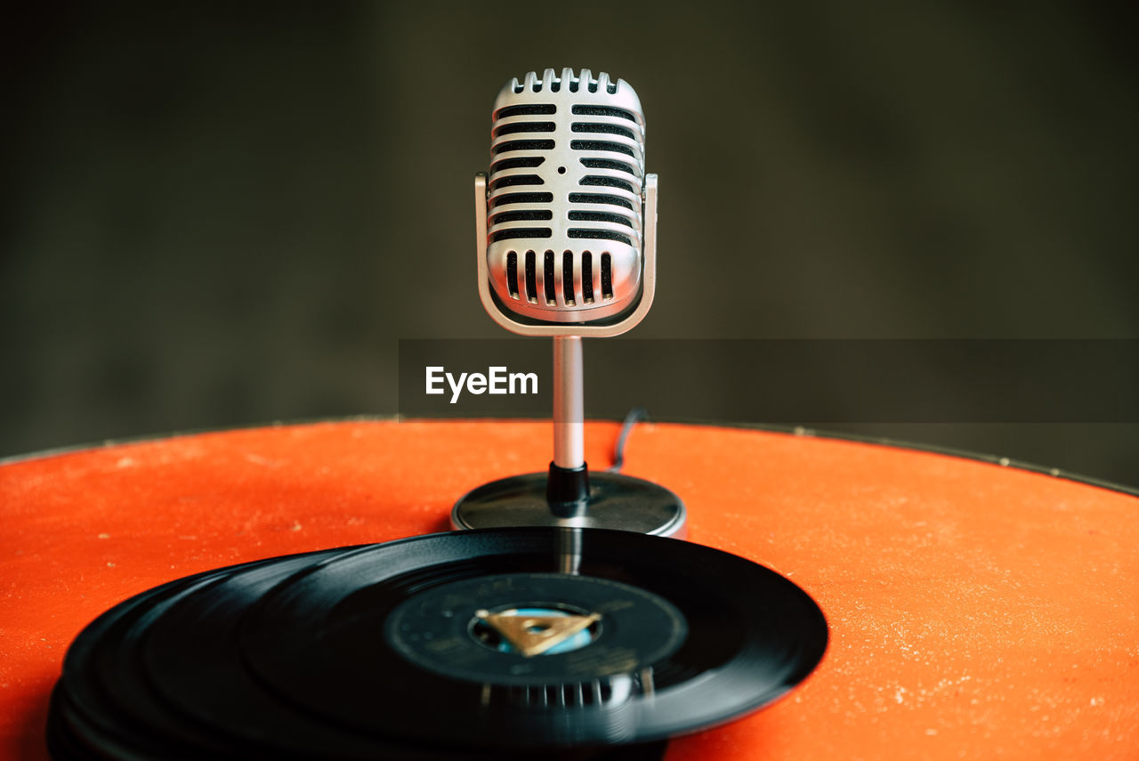 arts culture and entertainment, music, close-up, focus on foreground, indoors, black color, technology, no people, record, turntable, communication, retro styled, equipment, microphone, orange color, input device, audio equipment, red, number