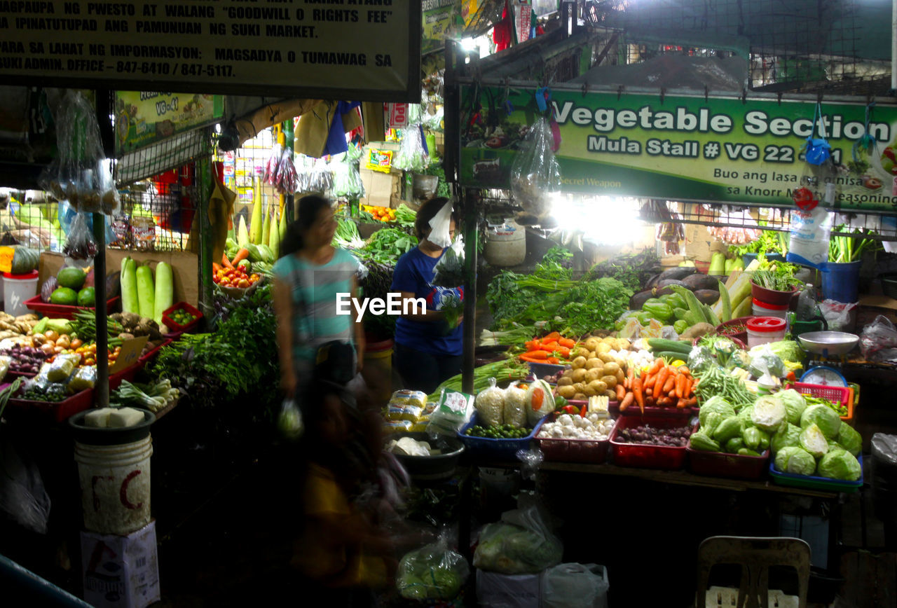 Blurred Image Of Women In Illuminated Vegetable Market At Night