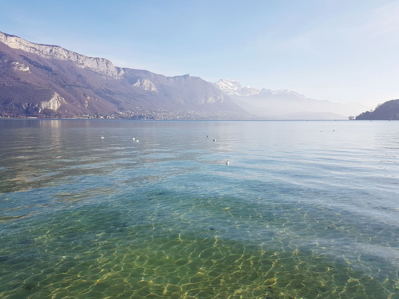 water, beauty in nature, scenics - nature, mountain, tranquil scene, waterfront, tranquility, sea, sky, idyllic, nature, day, no people, non-urban scene, blue, mountain range, outdoors, remote, turquoise colored, view into land