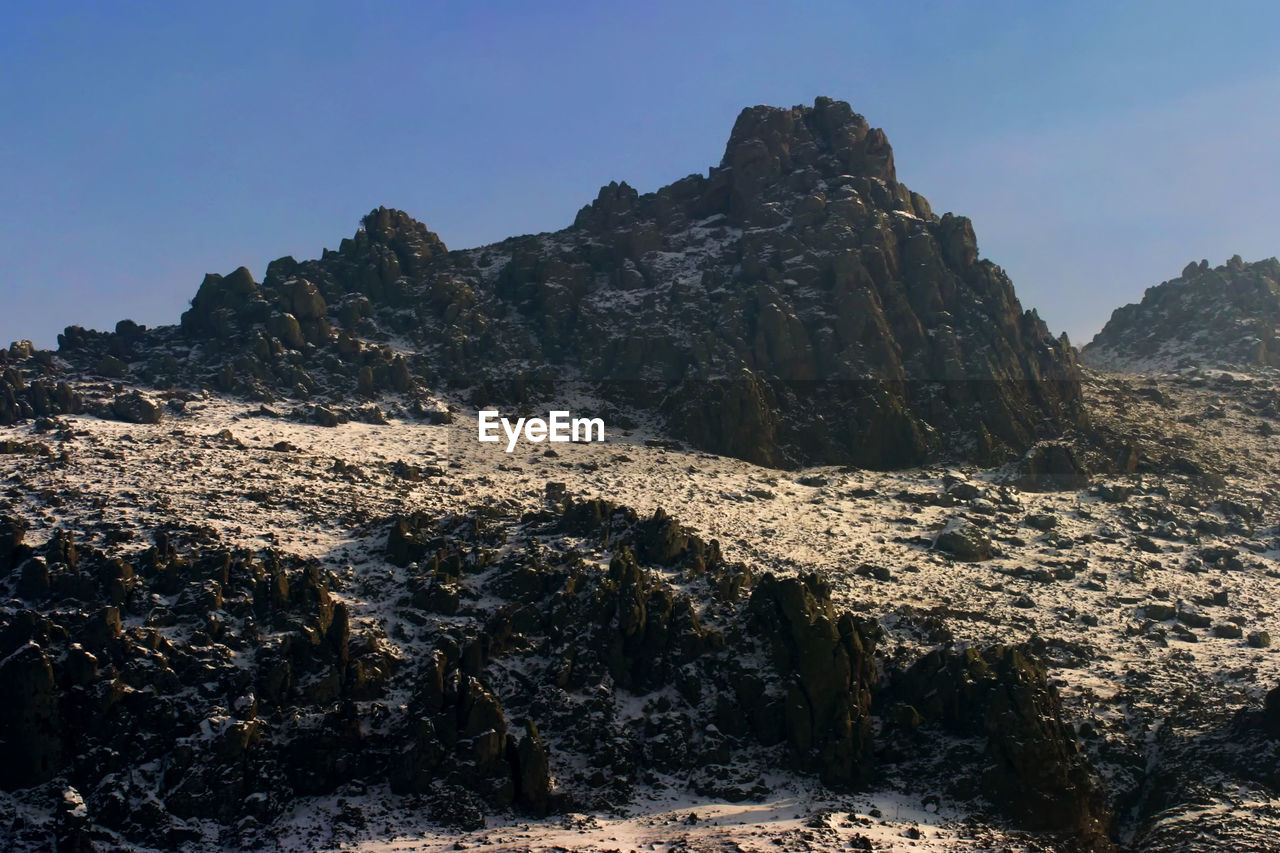 rock, rock - object, sky, solid, rock formation, mountain, beauty in nature, nature, scenics - nature, tranquility, no people, tranquil scene, clear sky, day, mountain range, geology, physical geography, environment, non-urban scene, land, outdoors, formation, mountain peak, eroded, arid climate