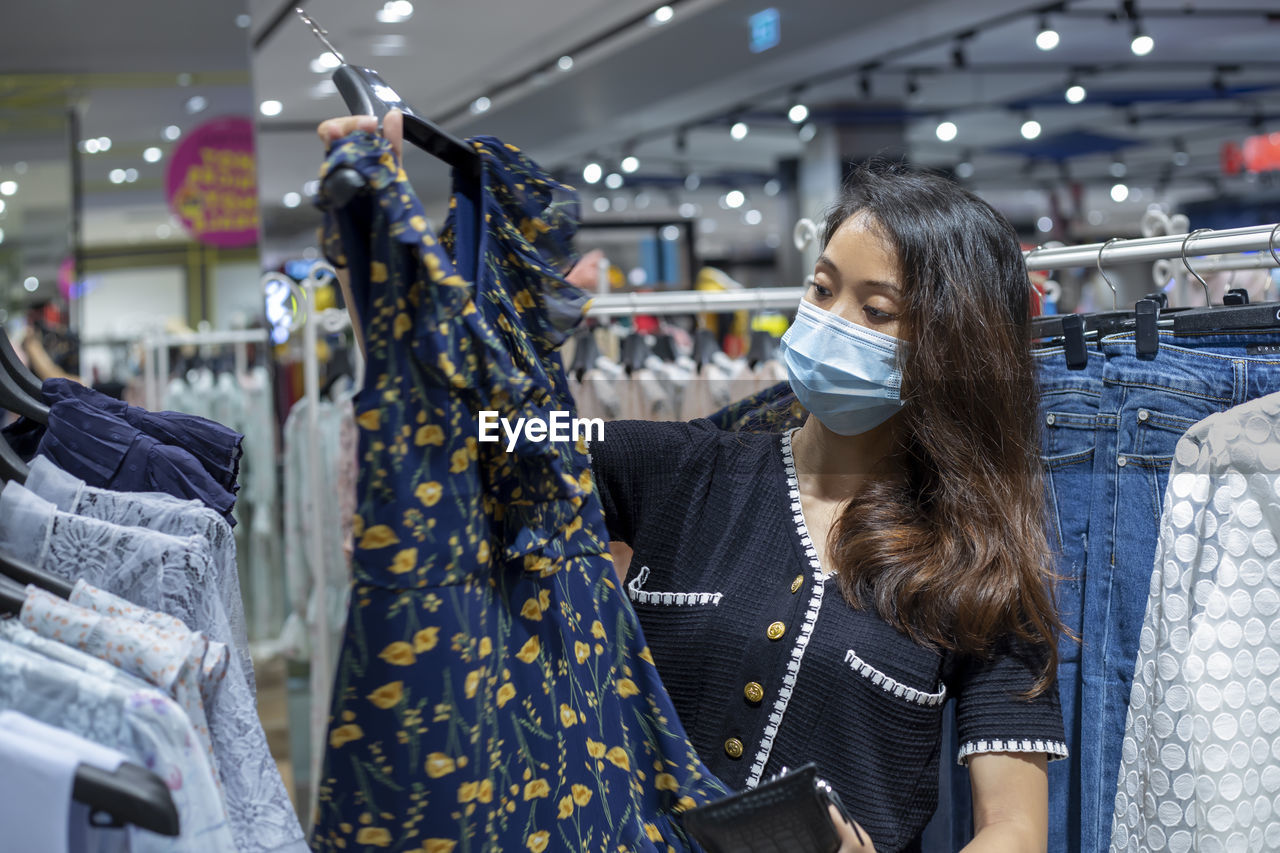 Young woman wearing mask shopping at clothing store