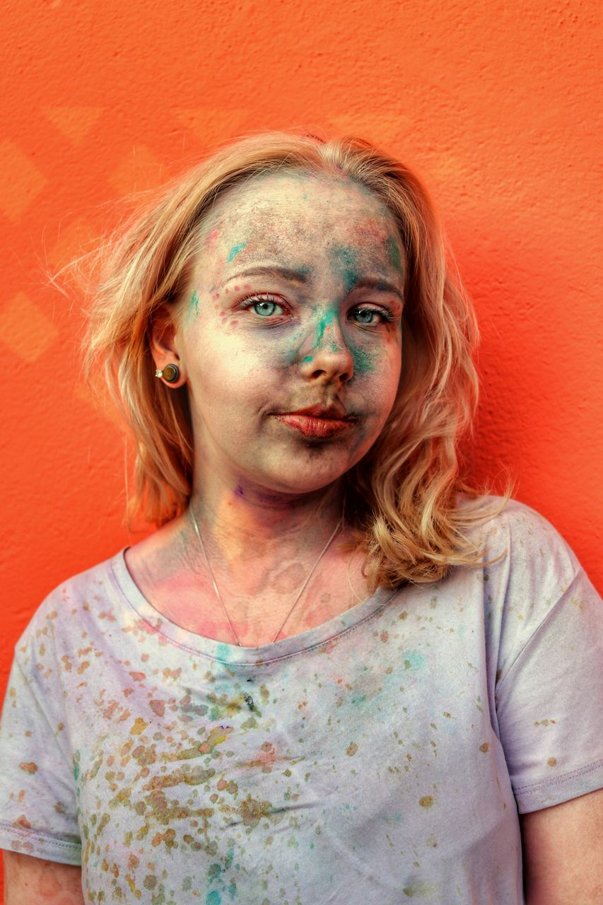 Portrait of teenage girl face covered powder paint standing against orange wall