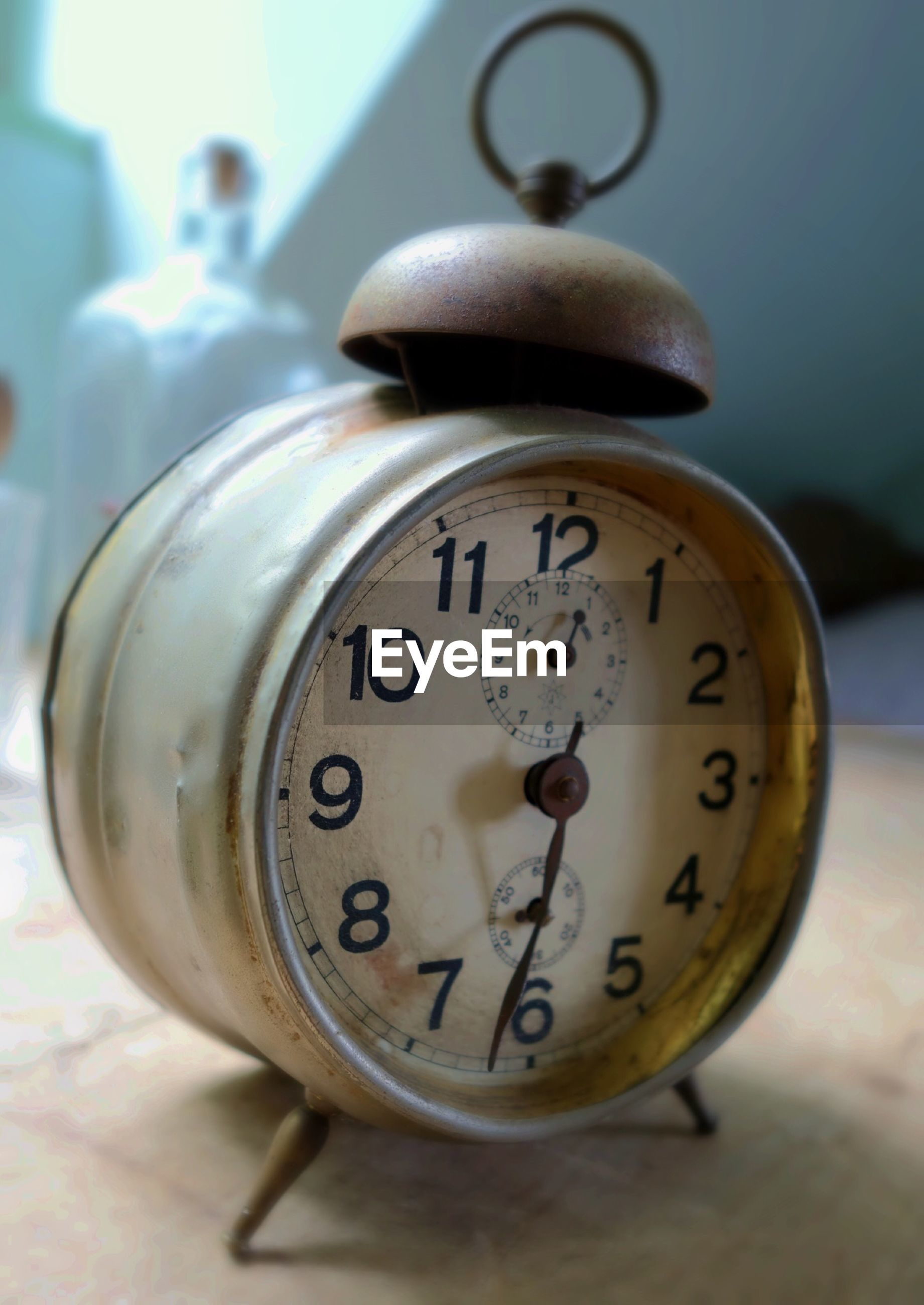 Close-up of old alarm clock on table at home