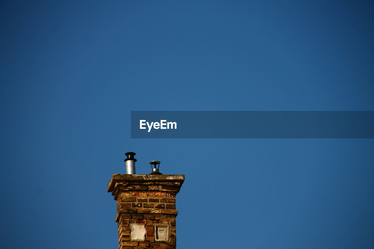 copy space, blue, sky, clear sky, architecture, built structure, bird, nature, no people, building exterior, vertebrate, low angle view, animal, day, animal themes, animals in the wild, perching, tower, building, one animal, outdoors
