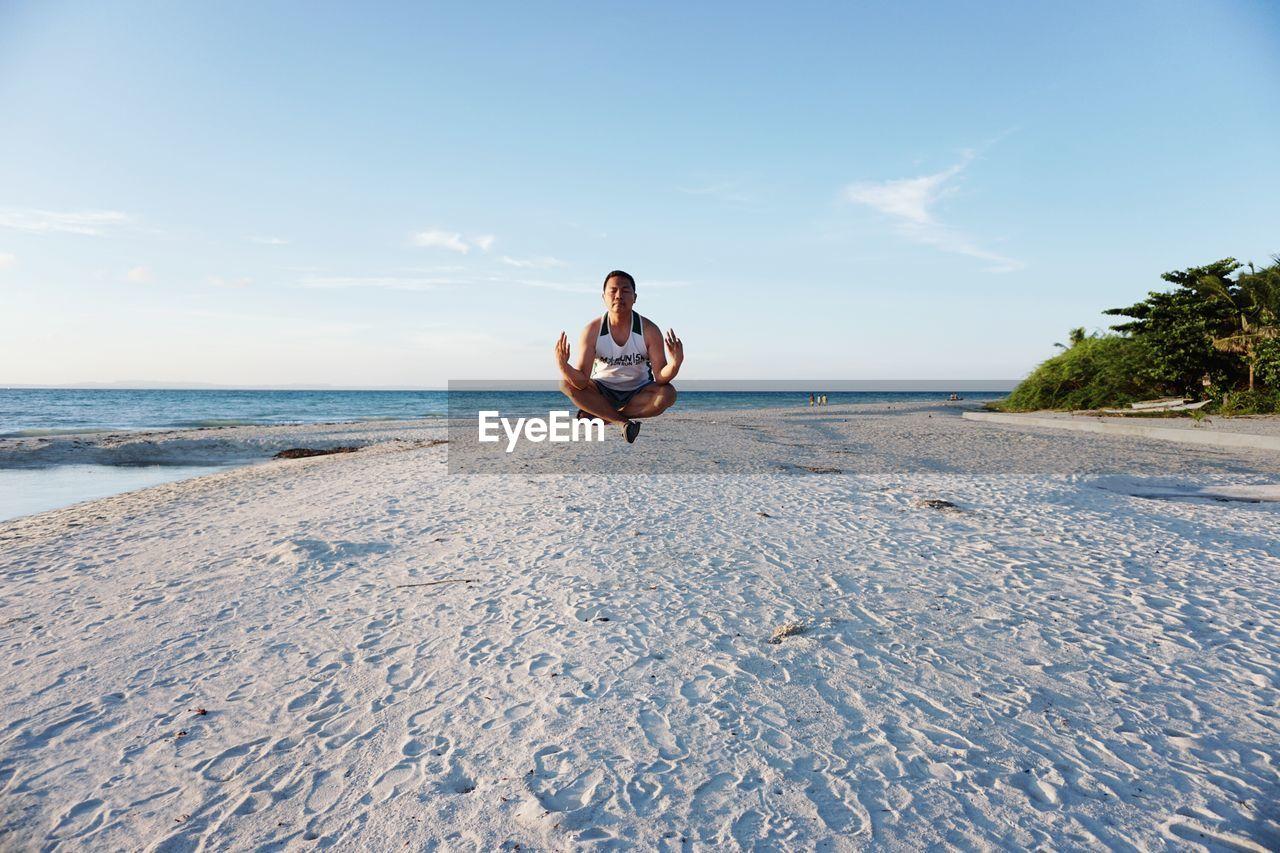 Man Meditating On Beach Against Sky