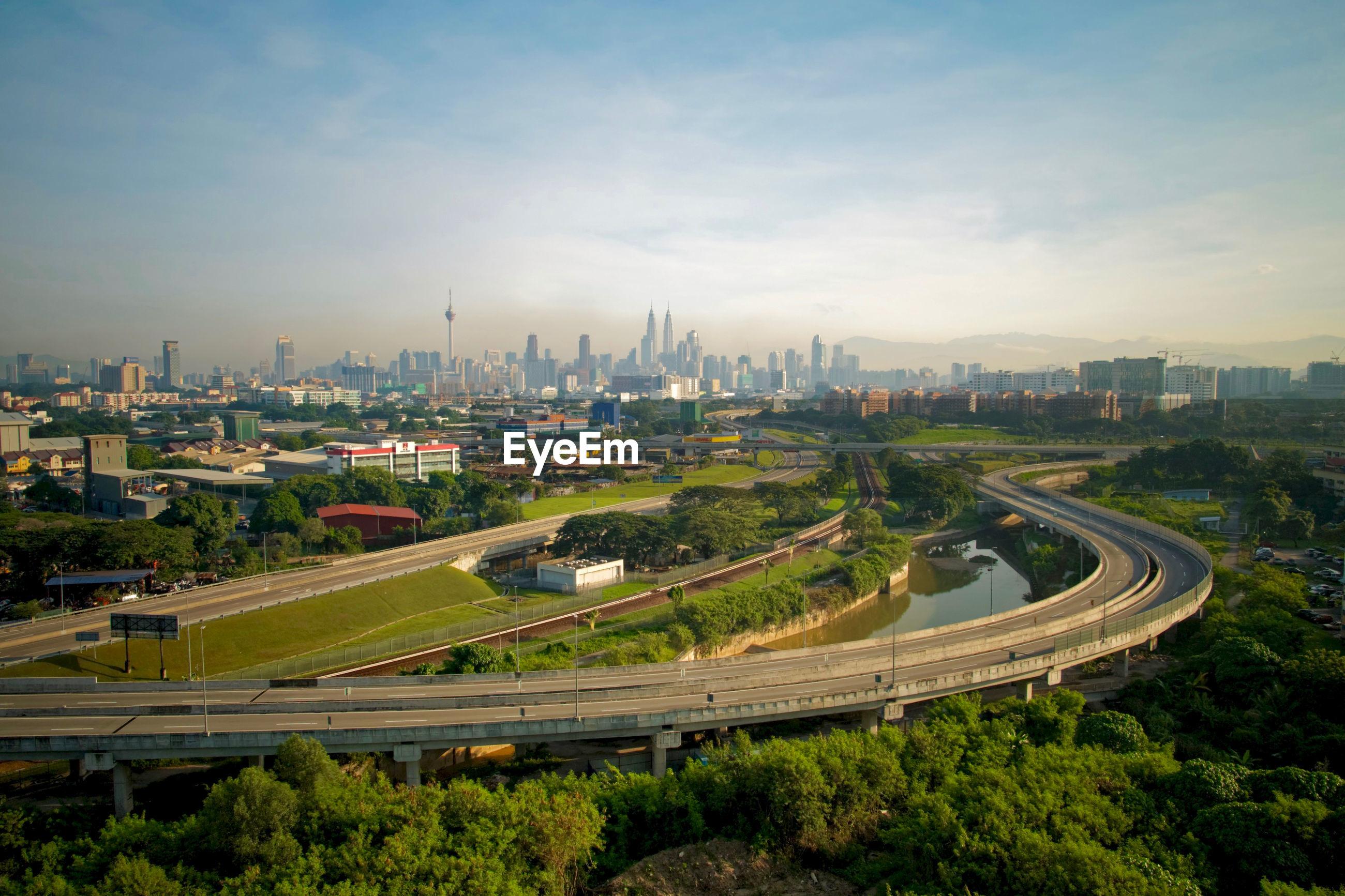 Bridge over river against cityscape