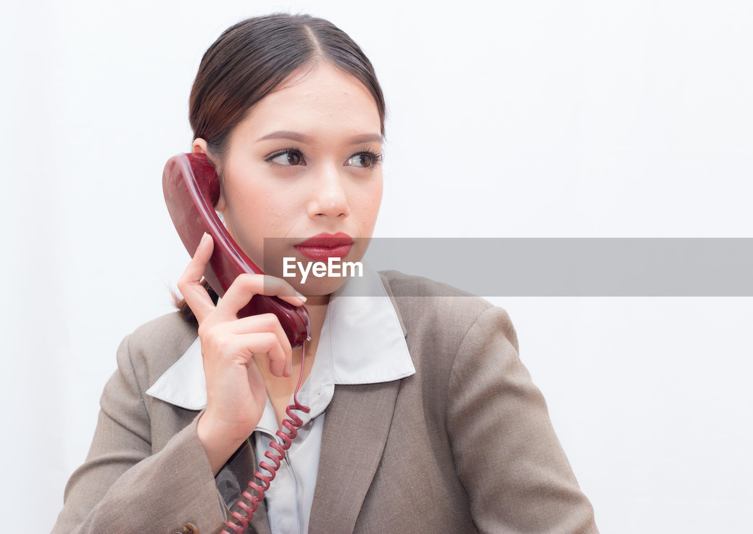 Businesswoman talking on telephone against white background