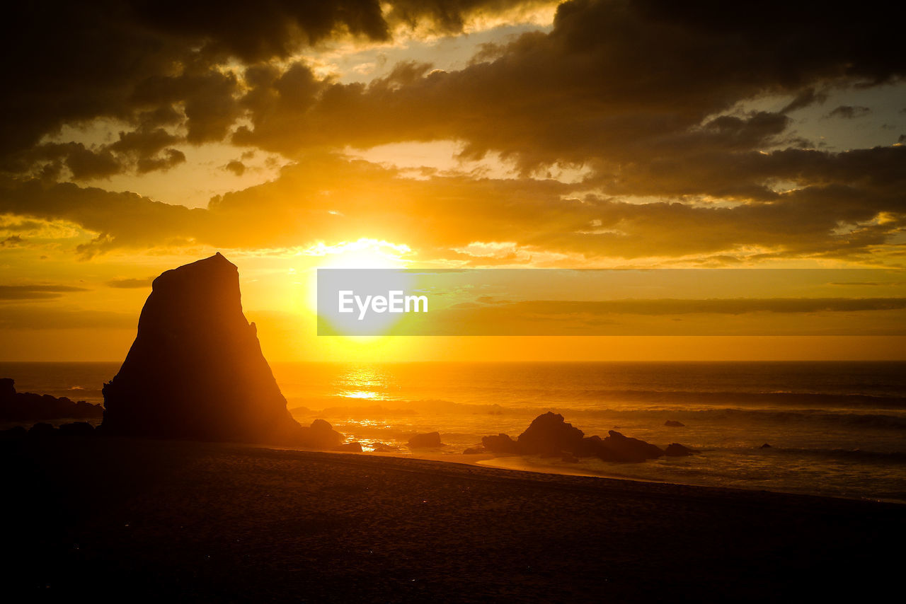 sunset, sky, scenics - nature, cloud - sky, sea, beauty in nature, orange color, rock, water, tranquil scene, land, solid, rock - object, nature, tranquility, idyllic, rock formation, beach, sunlight, no people, horizon over water, sun, outdoors, stack rock