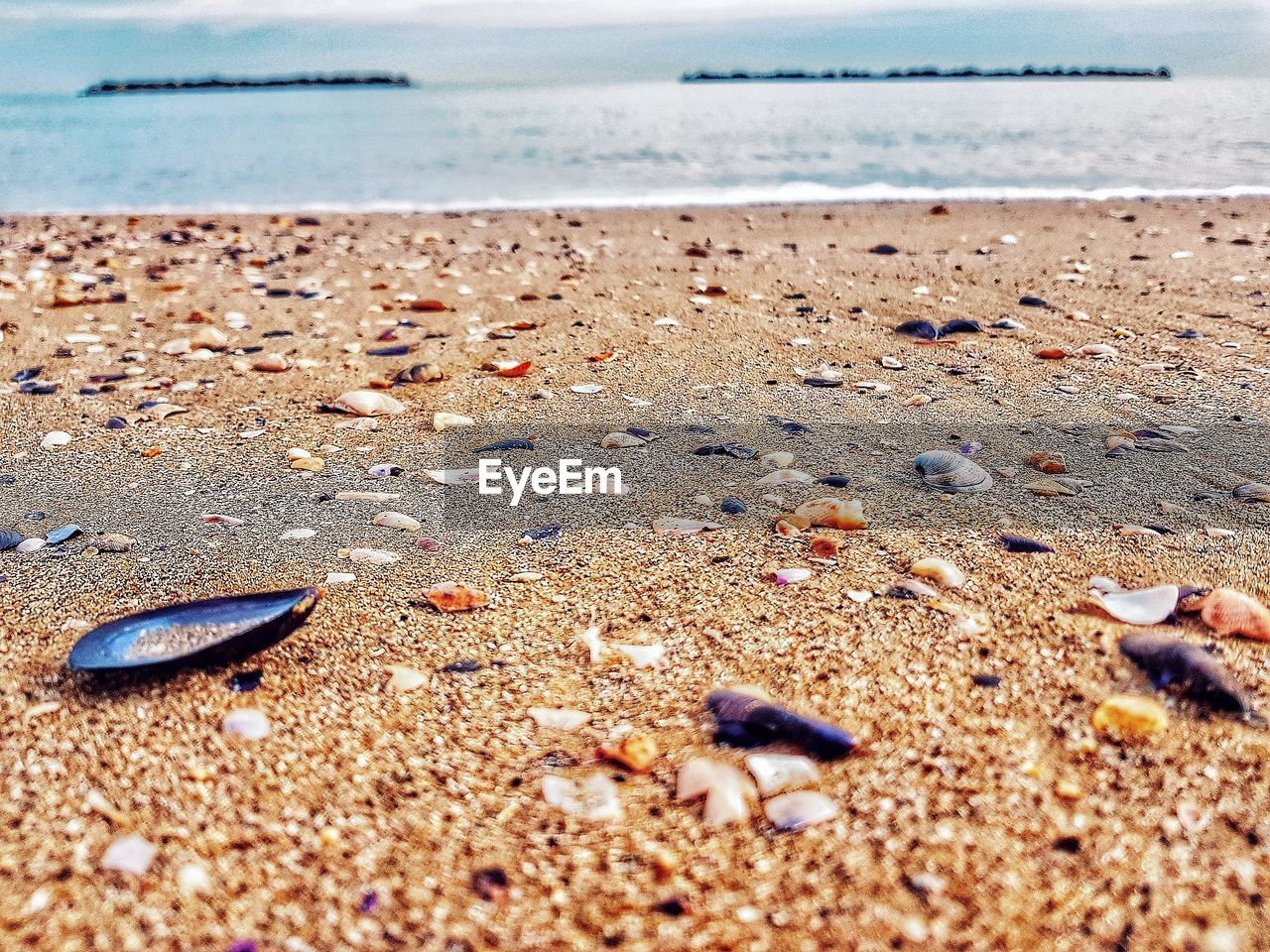 beach, sea, water, sand, shore, horizon over water, nature, tranquility, tranquil scene, beauty in nature, scenics, day, outdoors, no people, sunlight, close-up, pebble beach, sky