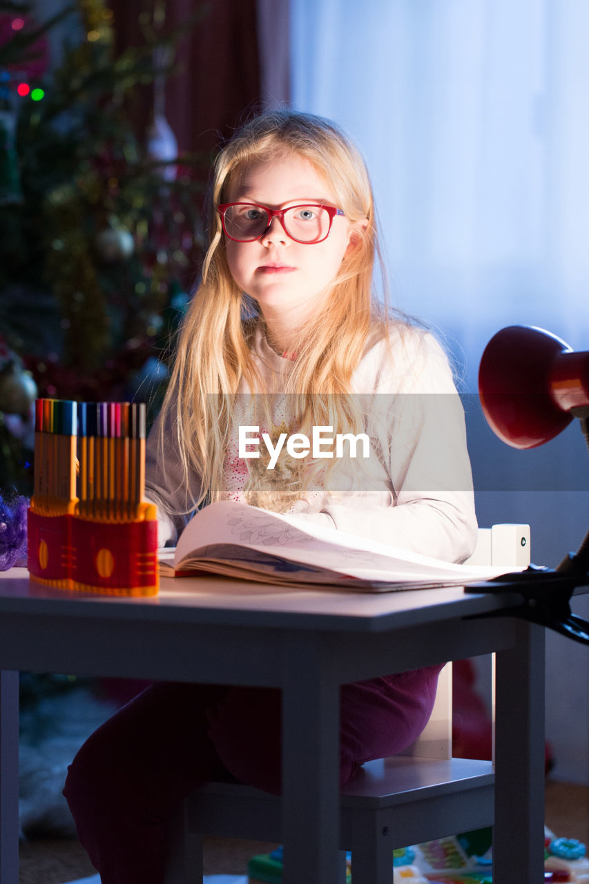 Portrait of girl studying at table during christmas