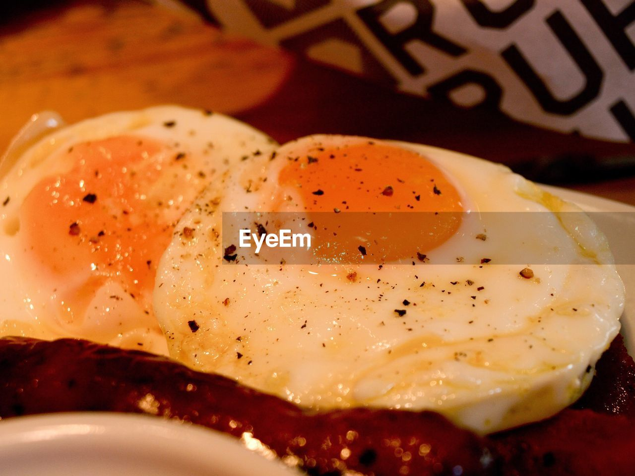 egg, egg yolk, breakfast, fried egg, food, food and drink, sunny side up, plate, pepper - seasoning, fried, no people, selective focus, indoors, close-up, bread, freshness, healthy eating, meal, toasted, poached, ready-to-eat, toasted bread