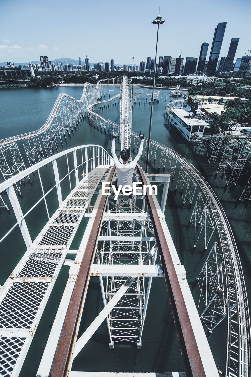 High Angle View Of Person With Arms Raised Sitting On Rollercoaster In City