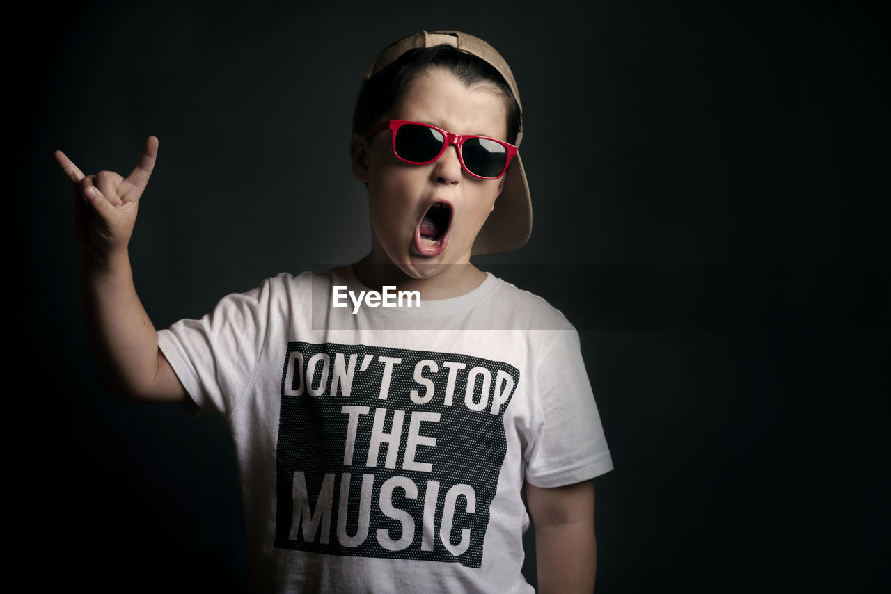 Boy wearing sunglasses showing horn sign against black background