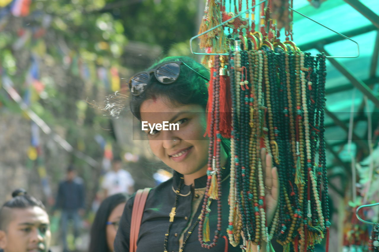 Portrait Of Smiling Woman Standing By Bead Necklace Hanging At Market Stall