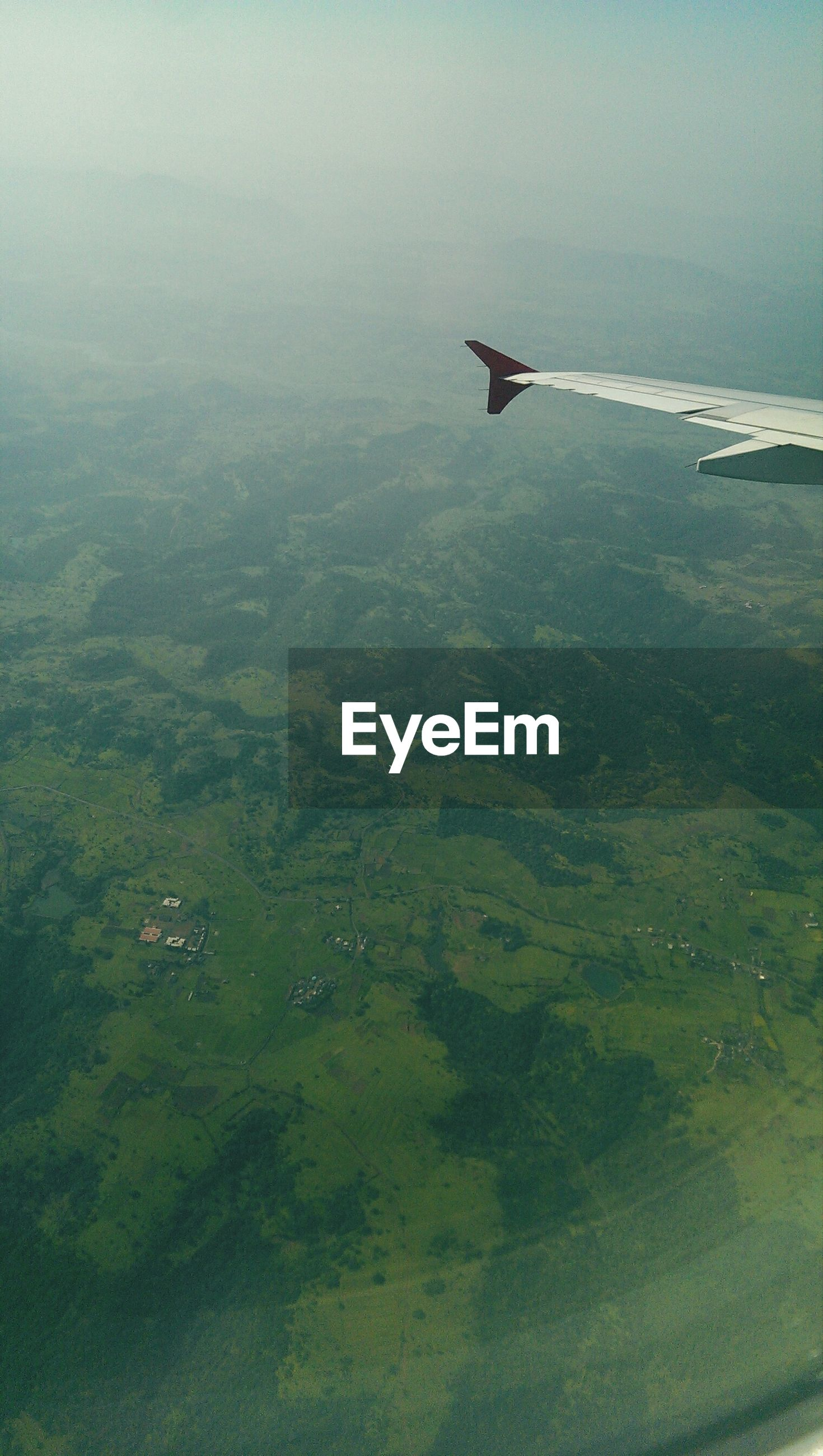 flying, transportation, aerial view, airplane, scenics, mode of transport, water, air vehicle, tranquil scene, beauty in nature, landscape, sea, nature, tranquility, travel, sky, aircraft wing, mountain, high angle view, mid-air
