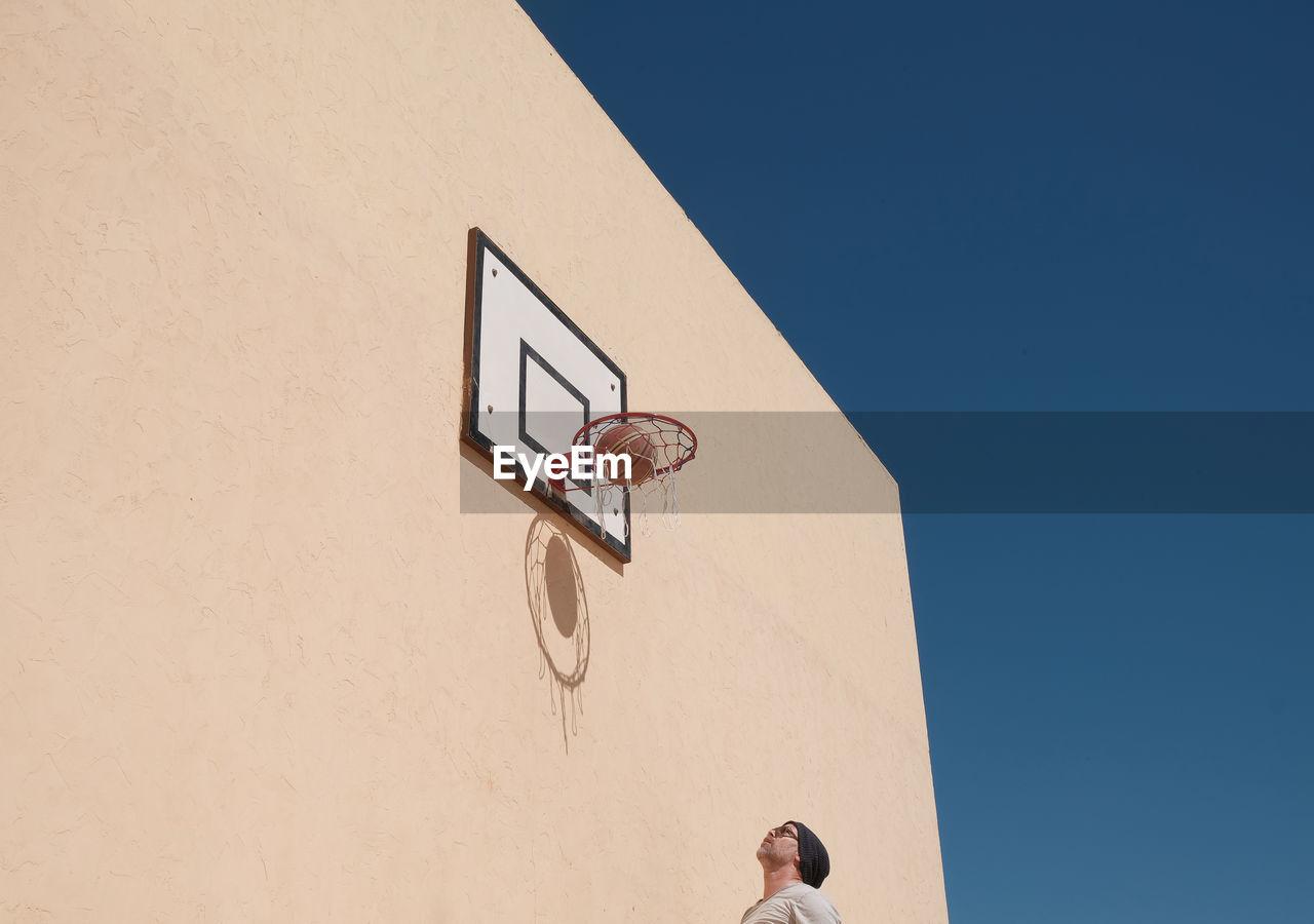 View Of Man Under Basketball Hoop Against Clear Sky