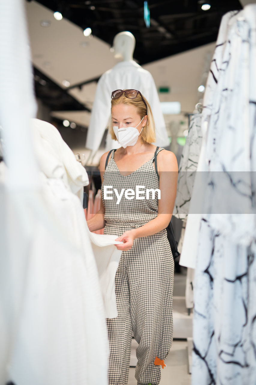 Mid adult woman wearing flu mask shopping in clothing store