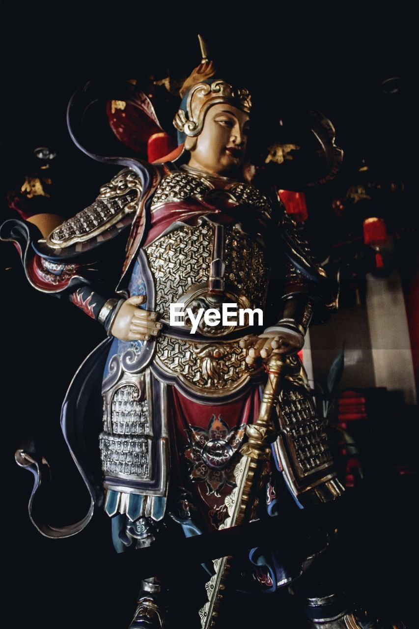 representation, art and craft, human representation, sculpture, indoors, no people, statue, architecture, male likeness, belief, spirituality, creativity, metal, black background, close-up, religion, history, the past, built structure, gold colored, ornate