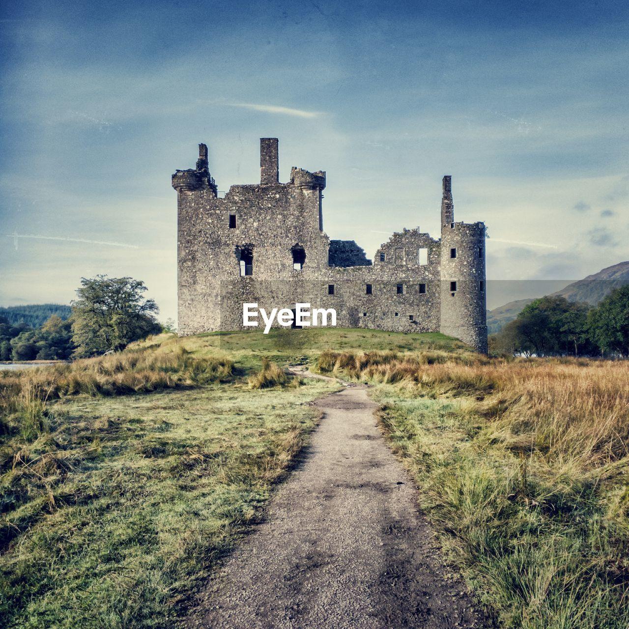 Empty Footpath Leading Towards Kilchurn Castle Against Sky