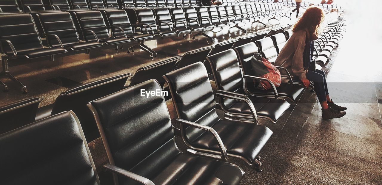 LOW SECTION OF MAN ON EMPTY CHAIRS IN ROW