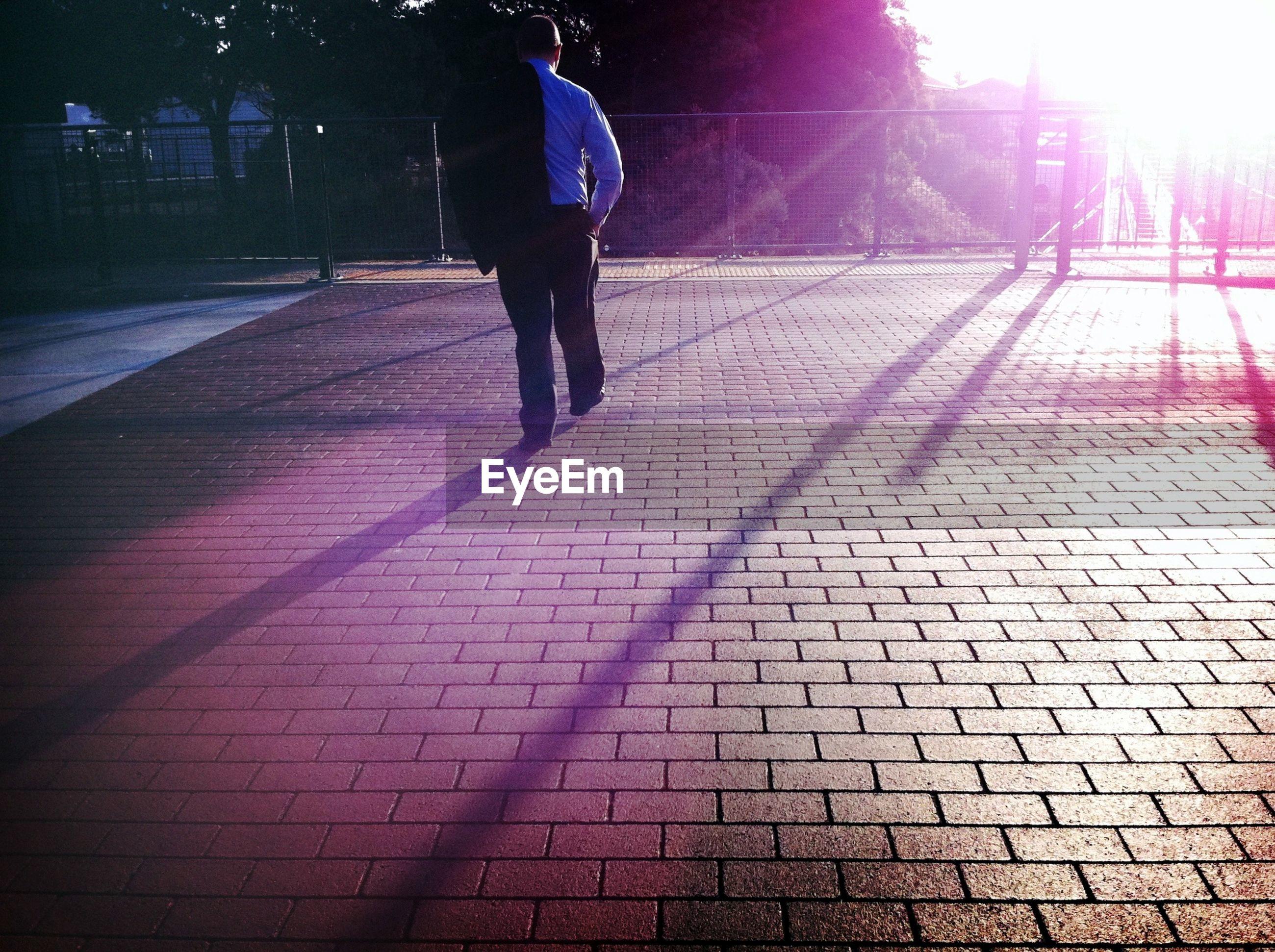 lifestyles, walking, cobblestone, rear view, sunlight, full length, leisure activity, the way forward, street, sidewalk, footpath, shadow, men, paving stone, person, standing, outdoors, sunbeam