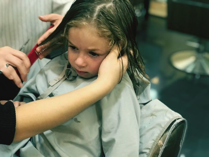 Cropped hand of hairdresser cutting girl hair in shop