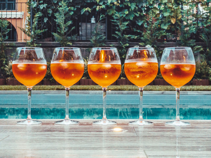 Close-up of aperol spritz against swimming pool