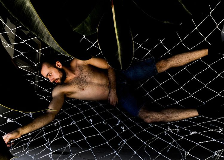 Full length of young man lying on hammock indoors